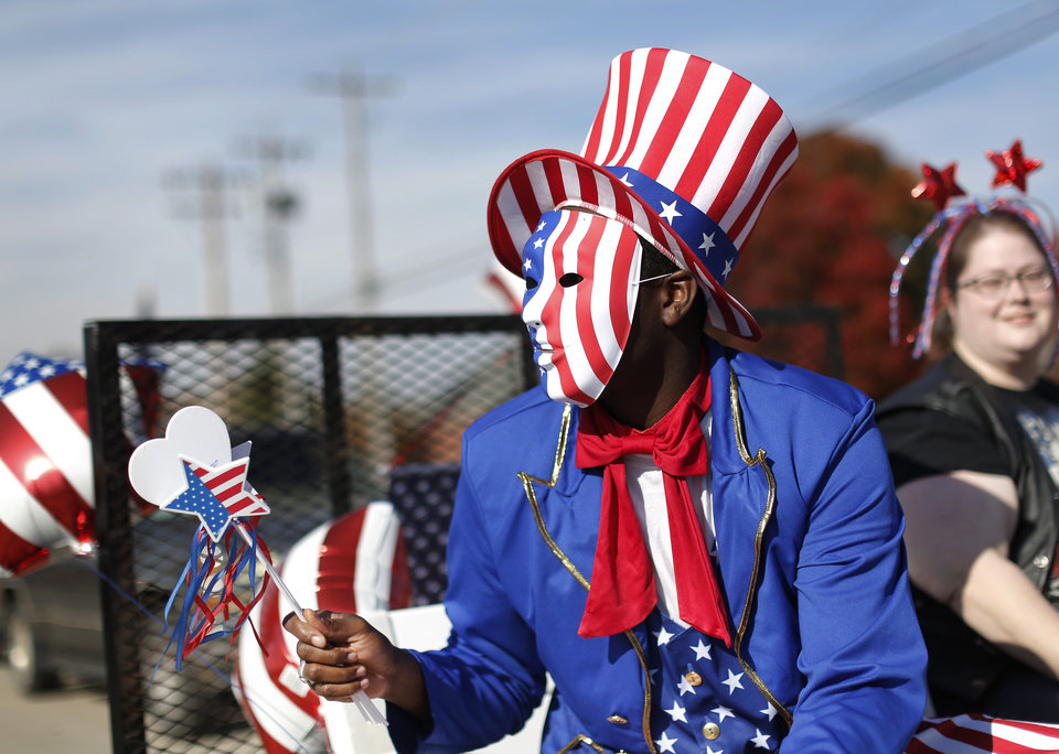 Photo - Patriotic costumes are worn by these people riding on a float in  the Midwest City Veteran's Day Parade on Friday, Nov. 10, 2017. Photo by Jim Beckel, The Oklahoman