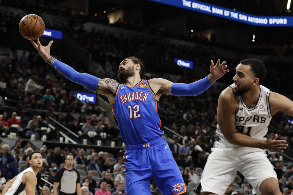 Photo - Oklahoma City Thunder center Steven Adams (12) reaches past San Antonio Spurs forward Trey Lyles (41) to grab a rebound during the first half of an NBA basketball game, in San Antonio, Thursday, Jan. 2, 2020. (AP Photo/Eric Gay)