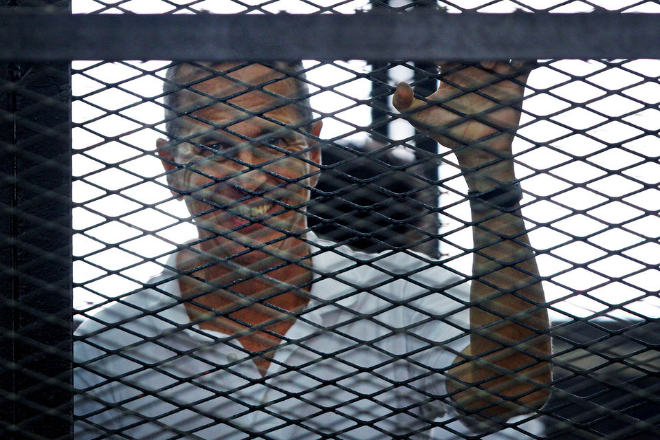 Photo - Al-Jazeera journalist Peter Greste looks out from the defendant's cage during the sentencing hearing for journalists working for Al-Jazeera in a courtroom in Cairo, Egypt, Monday, June 23, 2014. An Egyptian court on Monday convicted three journalists from Al-Jazeera English and sentenced them to seven years in prison each on terrorism-related charges, bringing widespread criticism that the verdict was a blow to freedom of expression. The three, Australian Peter Greste, Canadian-Egyptian Mohamed Fahmy and Egyptian Baher Mohammed, have been detained since December charged with supporting the Muslim Brotherhood, which has been declared a terrorist organization, and of fabricating footage to undermine Egypt's national security and make it appear the country was facing civil war. (AP Photo/Ahmed Abd El Latif, El Shorouk Newspaper)   EGYPT OUT