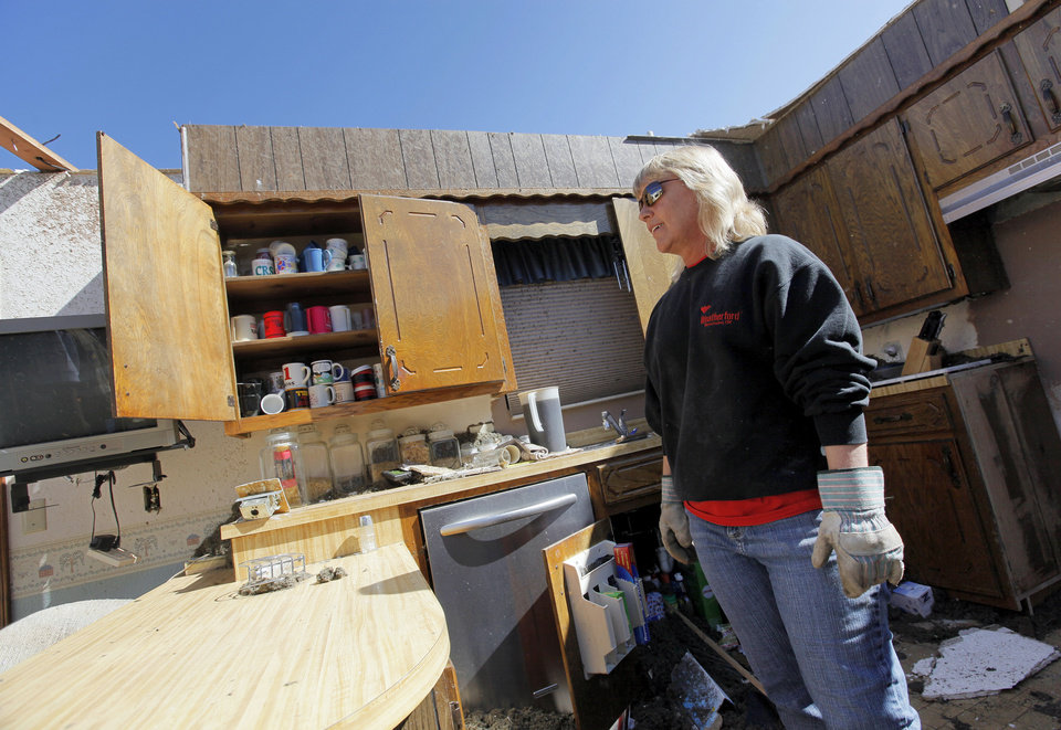 Photo - Andra Raymer stands in what is left of her kitchen in Woodward, Okla., Monday, April 16, 2012.  Raymer's home was destroyed when a tornado struck the town early Sunday morning. Photo by Nate Billings, The Oklahoman
