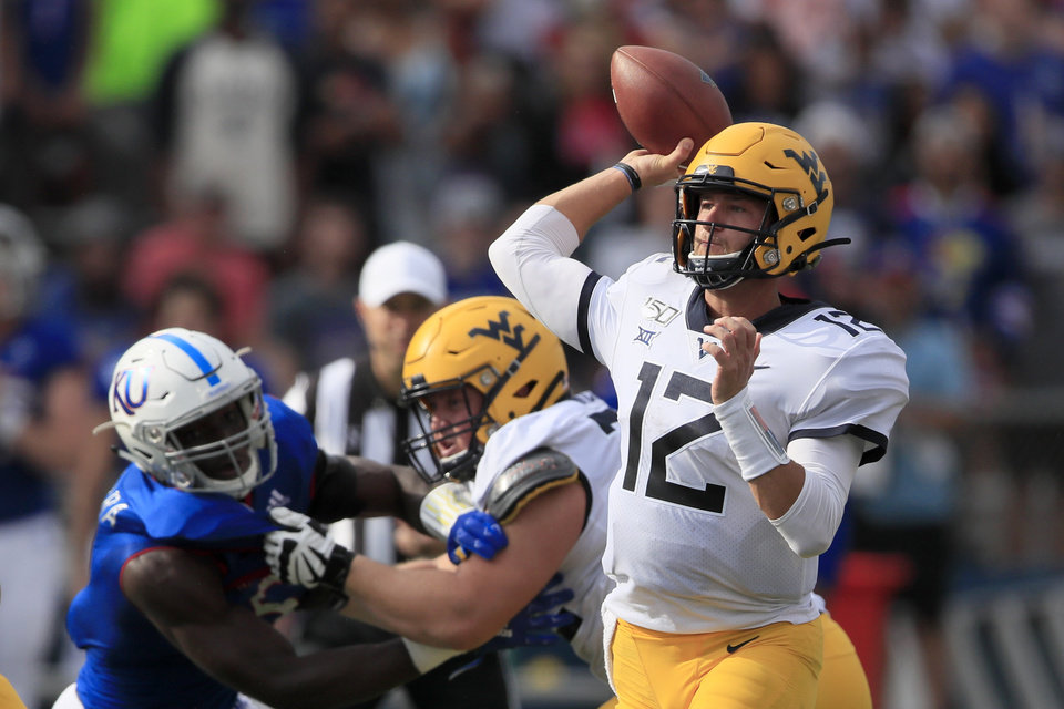 Photo - West Virginia quarterback Austin Kendall (12) passes to a teammate during the first half of an NCAA college football game against Kansas in Lawrence, Kan., Saturday, Sept. 21, 2019. Kendall passed for 202 yards in the game. West Virginia defeated Kansas 29-24. (AP Photo/Orlin Wagner)