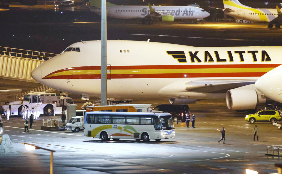 Photo -  A bus carrying U.S. passengers who were aboard the quarantined cruise ship the Diamond Princess arrives at Haneda airport in Tokyo, before the passengers board a Kalitta airplane chartered by the U.S. government Monday, Feb. 17, 2020. The cruise ship was carrying nearly 3,500 passengers and crew members under quarantine. (Sadayuki Goto/Kyodo News via AP)