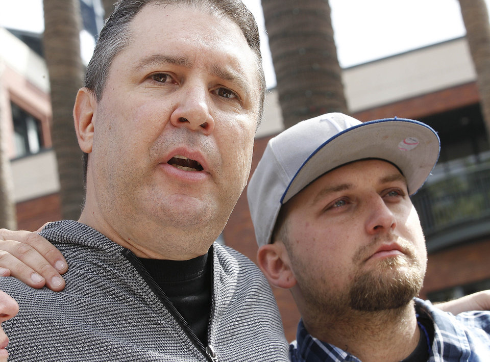Robert Preece and Robert Preece Jr., father and brother of Jonathan Denver, make a public plea for witnesses to Wednesday's fatal stabbing of Jonathan Denver, during a news conference outside AT&T Park before the Giants' baseball game in San Francisco, Sunday, Sept. 29, 2013. (AP Photo/Tony Avelar)