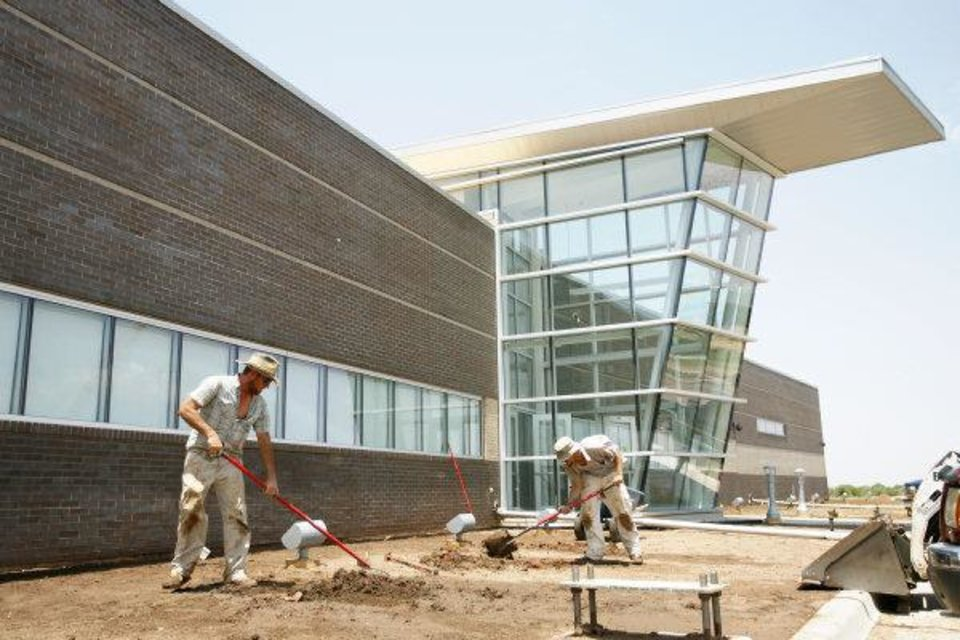 Larry Farnsworth and Cole Athay of Design Plus work on landscaping Monday at the Thunder's new practice facility. The team should be able to move into the building by August. <strong>ZACH GRAY - The Oklahoman</strong>
