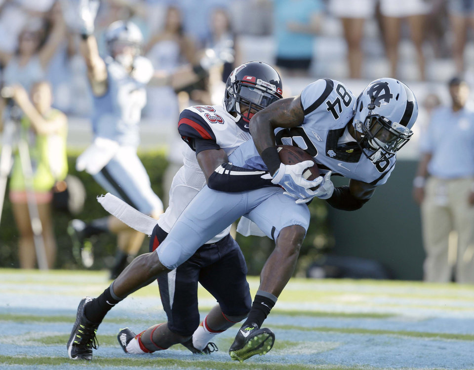 Photo - North Carolina's Bug Howard (84) runs the ball into the end zone for a touchdown as Liberty's Justin Guillory (23) tries to make the tackle during the first half of an NCAA college football game in Chapel Hill, N.C., Saturday, Aug. 30, 2014. (AP Photo/Gerry Broome)