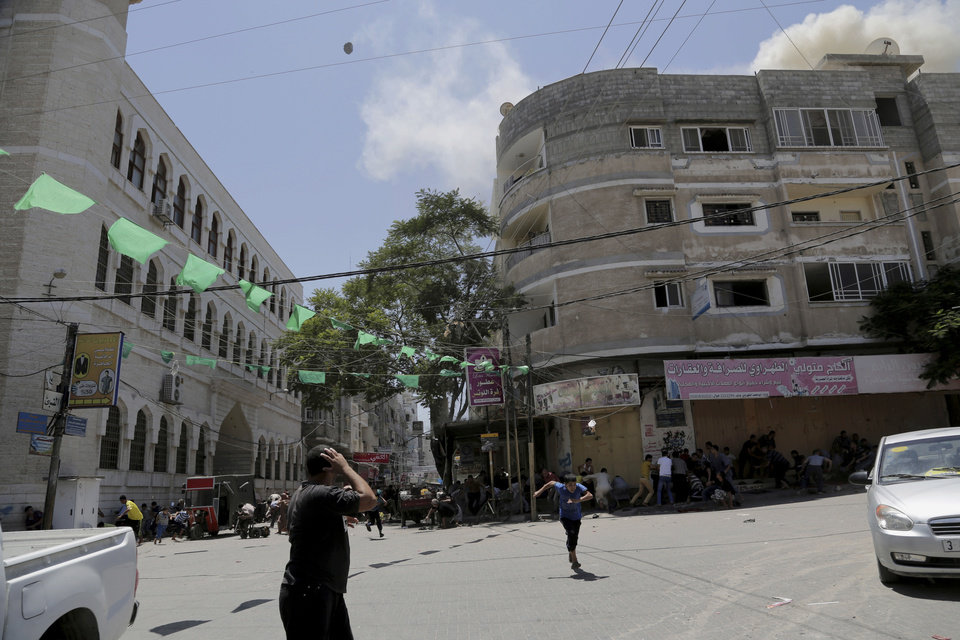 Photo - Palestinian worshipers and others run to take cover when an Israeli strike hit the roof of a building across from Al Qassam mosque, where they were offering Friday prayer in Nusseirat refugee camp in the central Gaza Strip on Friday, Aug. 1, 2014. (AP Photo/Adel Hana)