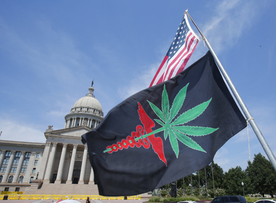 Photo - Flags  in support of medicinal marijuana initiative outside the Oklahoma State Capitol on Friday, August 15, 2014. [The Oklahoman Archives]