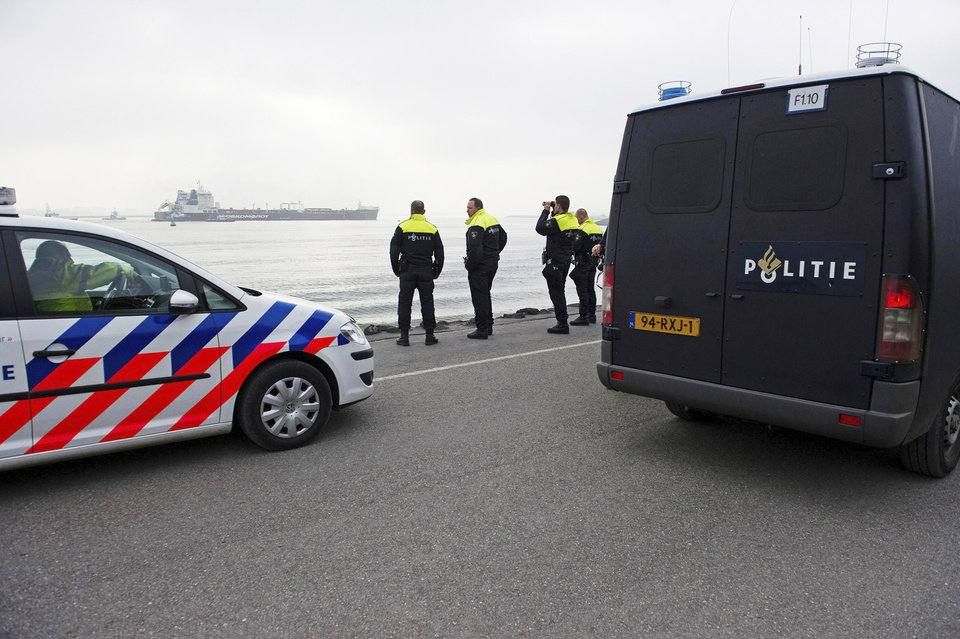 Photo - This image made available by environmental organization Greenpeace shows Dutch police looking on as Greenpeace activists aboard inflatable boats paint 'No Arctic Oil' on the side of the Mikhail Ulyanov oil tanker in Rotterdam, Netherlands, on Thursday, May 1, 2014. Greenpeace International activists are attempting to prevent a Russian tanker carrying the first oil from a new offshore platform in the Arctic from mooring at Rotterdam Port. The environmental group said Thursday it has sent two ships, Rainbow Warrior III and Esperanza, plus rubber rafts, paragliders and activists on shore, to meet the Mikhail Ulyanov, a tanker chartered by Russia's state-controlled oil company, Gazprom OAO. (AP Photo/Marten van Dijl, Greenpeace) NO SALES, NO ARCHIVE