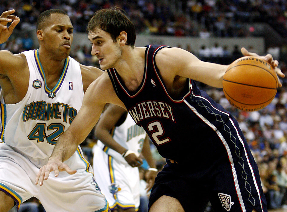 Photo - New Jersey Nets center Nenad Krstic (12) of Serbia drives the ball past New Orleans/Oklahoma City Hornets center PJ Brown (42) in the first half of an NBA basketball game Sunday, March. 12, 2006, in Oklahoma City. (AP Photo/Ty Russell)