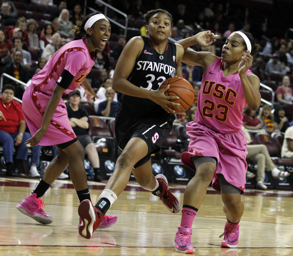 Photo - Stanford guard Amber Orrange (33) drives to the basket against Southern California forward Desiree Bradley, left, and guard Brianna Barrett (23) duirng the first half of an NCAA college basketball game Friday, Feb. 21, 2014, in Los Angeles. (AP Photo/Alex Gallardo)