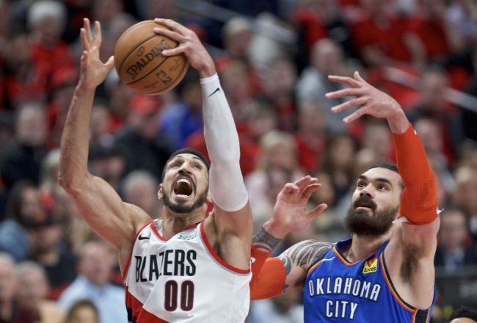 Photo -  Portland'sr Enes Kanter, left, rebounds the ball next to Oklahoma City's Steven Adams during Tuesday night's Game 2 of the NBA playoffs in Portland, Ore. Kanter ran into foul trouble and was not as effective as he was in Game 1 vs. OKC. [AP Photo/Craig Mitchelldyer]