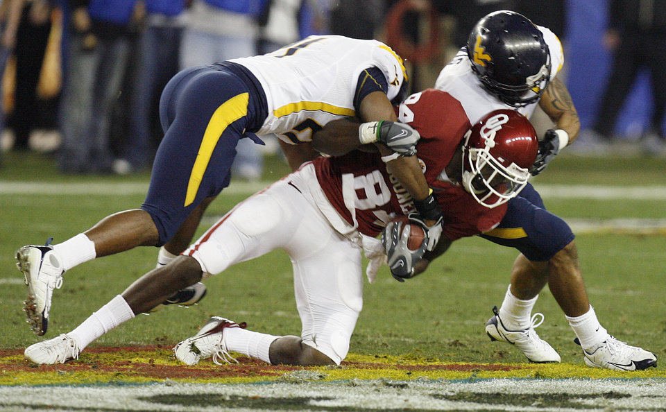 Photo - West Virginia's Ryan Mundy (21) and Antonio Lewis (6) bring down Oklahoma's Quentin Chaney (84) during the first half of the Fiesta Bowl college football game between the University of Oklahoma Sooners (OU) and the West Virginia University Mountaineers (WVU) at The University of Phoenix Stadium on Wednesday, Jan. 2, 2008, in Glendale, Ariz. 