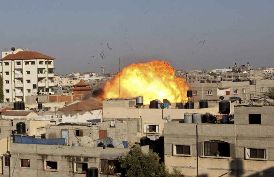 Photo - A ball of fire rises from an explosion following an Israeli air strike on the house of Nafez Azzam, a leader for Islamic Jihad leader, one hour before the announcement of the cease-fire between Palestinians and Israelis, in Rafah refugee camp, in the southern Gaza Strip, Tuesday, Aug. 26, 2014. (AP Photo/Hatem Ali)