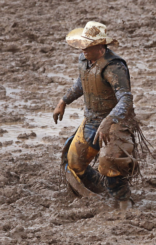 Photo - Cody Godinez, Clines Corners, NM, gets up out of the mud after being thrown in the Saddle Bronc competition at the International Youth Finals Rodeo in Shawnee at the Heart of Oklahoma Exposition Center, Wednesday, July 9, 2014. Photo by David McDaniel, The Oklahoman