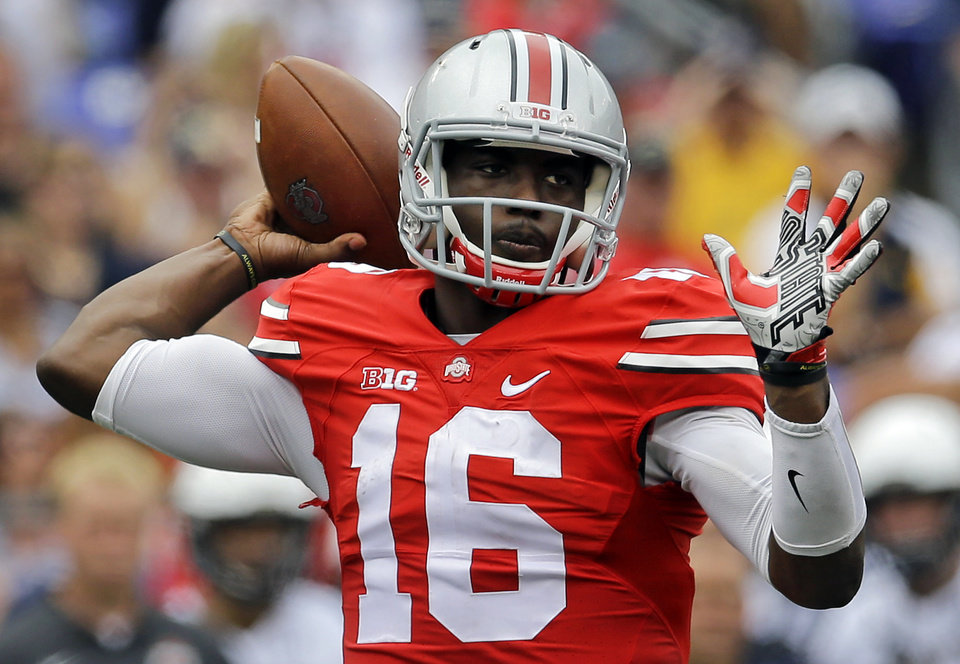 Photo - Ohio State quarterback J.T. Barrett throws to a receiver in the first half of an NCAA college football game against Navy in Baltimore, Saturday, Aug. 30, 2014. (AP Photo/Patrick Semansky)