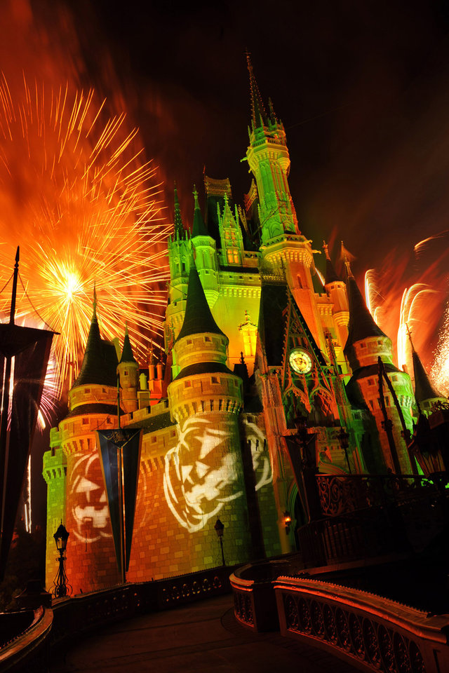 Photo -   This undated image released by Disney shows orange fireworks exploding over Cinderella's Castle while illuminated pumpkins are projected with light during the