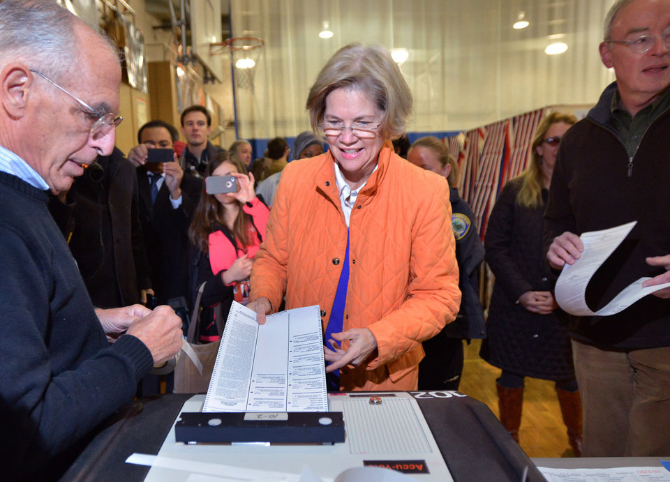 Democratic candidate for U.S. Senate Elizabeth Warren, center, casts her ballot as she and her husband , Bruce Mann, right, visited the polls near their Cambridge, Mass. home on Election Day, Tuesday, Nov. 6, 2012. Warren is running against Sen. Scott Brown (R-MA), who was elected in a special election in 2010 after the death of Sen. Ted Kennedy (D-MA). (AP Photo/Josh Reynolds)