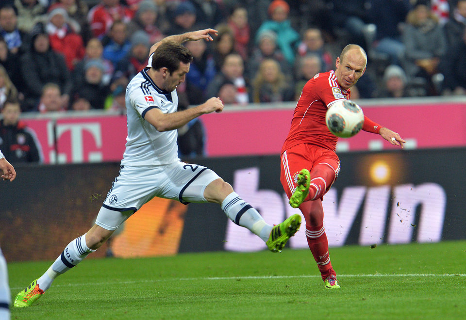 Photo - Bayern's Arjen Robben of the Netherlands, right, and Schalke's Christian Fuchs of Austria challenge for the ball, during  the German first division Bundesliga soccer match between  FC Bayern Munich and FC Schalke in Munich, Germany, on Saturday, March 1, 2014. (AP Photo/Kerstin Joensson)