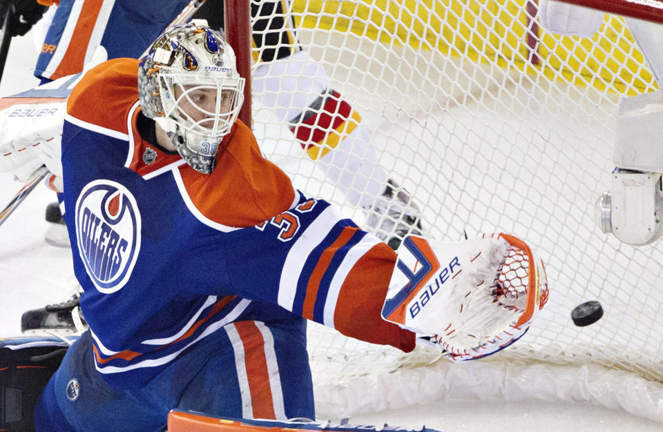 Photo - Edmonton Oilers goalie Viktor Fasth (35) gives up a goal to the Calgary Flames during the second period of an NHL hockey game Saturday, March 22, 2014, in Edmonton, Alberta. (AP Photo/The Canadian Press, Jason Franson)