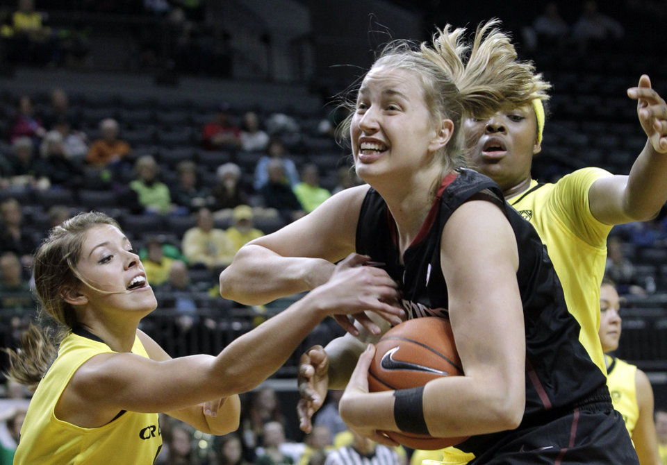 Stanford forward Mikaela Ruef, center, is double-teamed under the basket by Oregon's Devyn Galland, left, and Jillian Alleyne during the first half of an NCAA college basketball game in Eugene, Ore., Friday, Feb. 1, 2013. (AP Photo/Don Ryan)