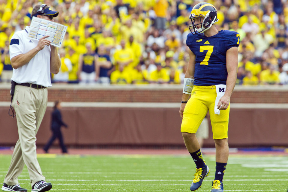Photo - Michigan quarterback Shane Morris (7) gets direction from offensive coordinator Doug Nussmeier, left, between downs in the third quarter of an NCAA college football game against Appalachian State in Ann Arbor, Mich., Saturday, Aug. 30, 2014. Michigan won 52-14. (AP Photo/Tony Ding)