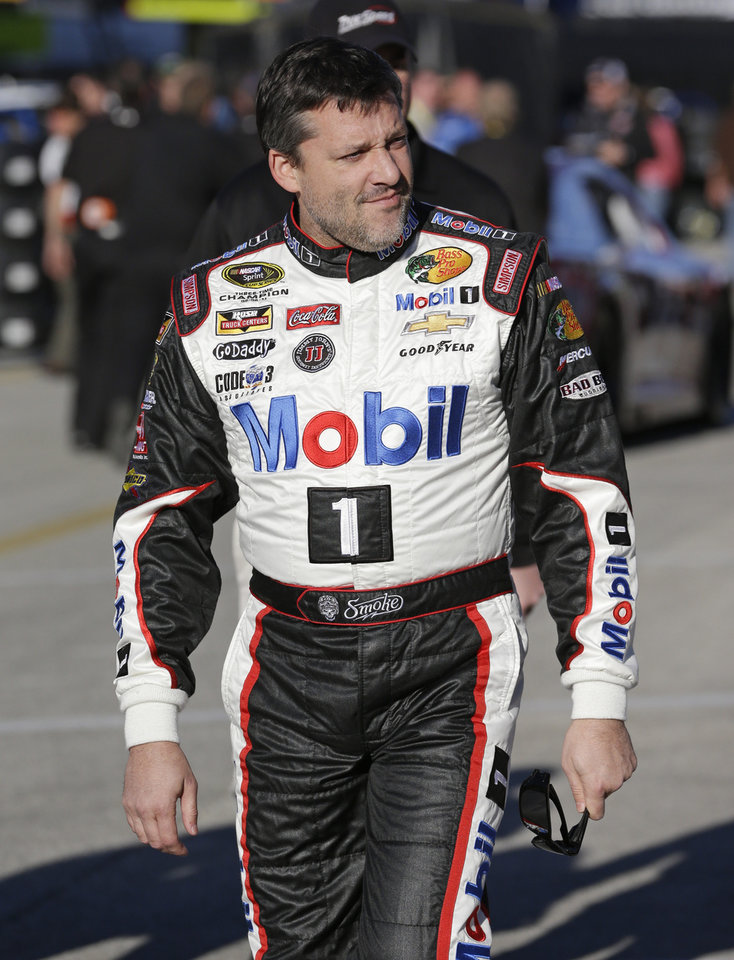 Photo - Tony Stewart walks to his garage before practice for the Sprint Unlimited auto race at Daytona International Speedway in Daytona Beach, Fla., Friday, Feb. 14, 2014. Stewart has not raced in more than six months since he broke two bones in his leg in an August sprint-car crash.(AP Photo/John Raoux)