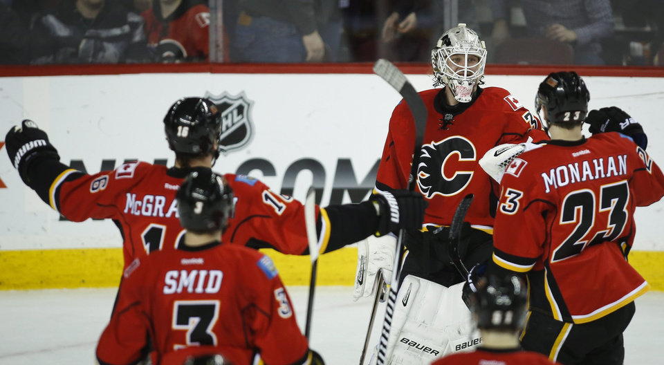 Photo - Calgary Flames goalie Karri Ramo, centre, from Finland, celebrates with teammates following their overtime win in NHL hockey action against the San Jose Sharks in Calgary, Monday, March 24, 2014. The Flames beat the Sharks 2-1 in a shootout. (AP Photo/The Canadian Press, Jeff McIntosh)