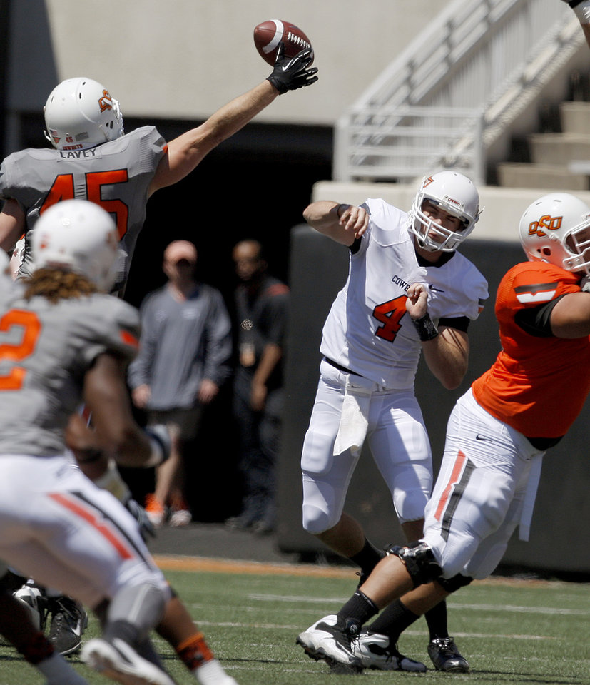 Photo - OSU's J.W. Walsh has his pass batted down by  Caleb Lavey during Oklahoma State's spring football game at Boone Pickens Stadium in Stillwater, Okla., Saturday, April 21, 2012. Photo by Bryan Terry, The Oklahoman