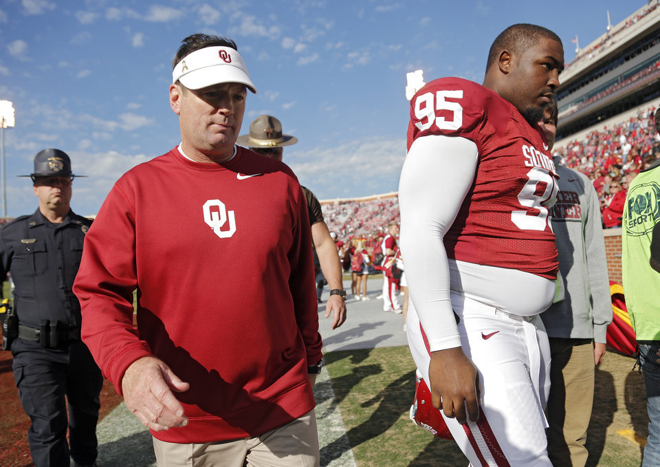 Bob Stoops walks off the field with Oklahoma's Quincy Russell (95) after the Sooners 48-10 win over Iowa State in the college football game between the University of Oklahoma Sooners (OU) and the Iowa State University Cyclones (ISU) at Gaylord Family-Oklahoma Memorial Stadium in Norman, Okla. on Saturday, Nov. 16, 2013. Photo by Chris Landsberger, The Oklahoman