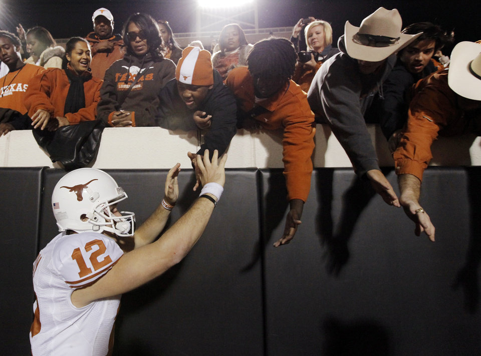 Photo - Texas quarterback Colt McCoy (12) celebrates with Texas fans after the college football game between the Oklahoma State University Cowboys (OSU) and the University of Texas Longhorns (UT) at Boone Pickens Stadium in Stillwater, Okla., Saturday, Oct. 31, 2009. Texas won, 41-14. Photo by Nate Billings, The Oklahoman