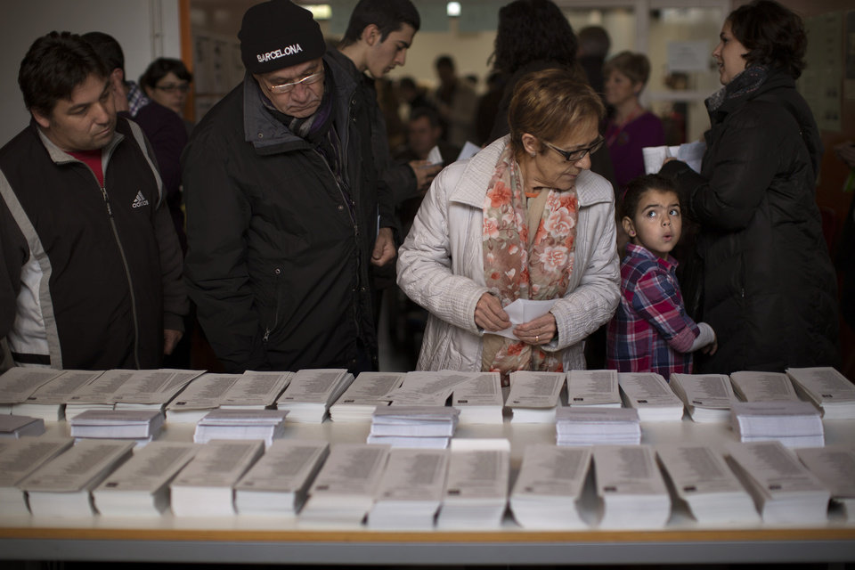 Photo -   Voters choice their ballot papers to cast their votes in a polling station in Barcelona, Spain, on Sunday, Nov. 25, 2012. Voters in Catalonia begin casting their ballots in regional elections that could determine the future shape of Spain. If voters give the regional government strong support, its leader pledged to hold a referendum asking Catalans if they'd prefer to split from Spain and go it alone in the 27-member EU. (AP Photo/Emilio Morenatti)