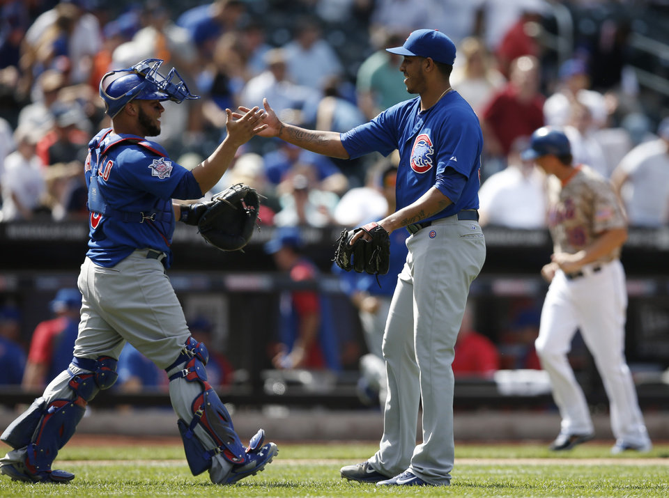 Photo - Chicago Cubs catcher Welington Castillo (5) congratulates Cubs relief pitcher Hector Rondon after the Cubs beat the New York Mets 4-1 in a baseball game at Citi Field in New York, Monday, Aug. 18, 2014. (AP Photo/Kathy Willens)