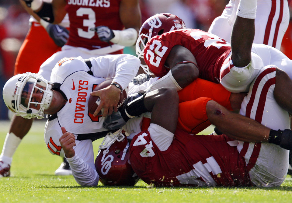 OSU's Zac Robinson (11) is taken down by Oklahoma's Keenan Clayton (22) and Jeremy Beal (44) during the first half of the Bedlam college football game between the University of Oklahoma Sooners (OU) and the Oklahoma State University Cowboys (OSU) at the Gaylord Family -- Oklahoma Memorial Stadium on Saturday, Nov. 28, 2009, in Norman, Okla.  Photo by Chris Landsberger, The Oklahoman