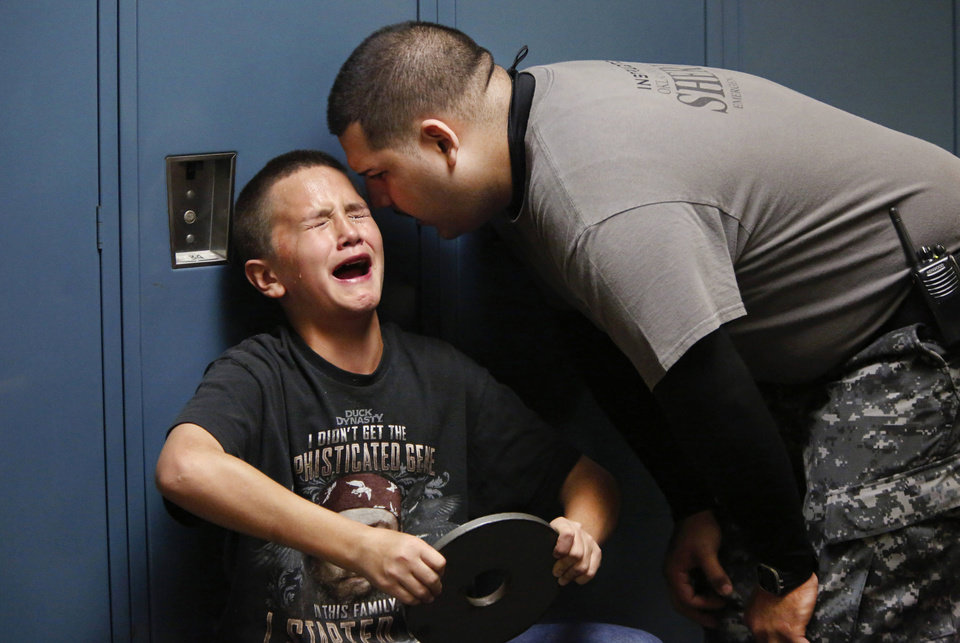 Photo - Tears rolling down his face, this boy screams out as a deputy gets right into his ear to tell him he needs to stop crying and finish the physical activity he was assigned to do. Knees bent in a semi-seated position, the boy leans against a locker and is told to push his arms out in front of him while holding a weight. Reality Check is a program that allows at-risk students to spend an afternoon in the Oklahoma County jail and tour the jail while inmates try to scare them straight. Photo taken Tuesday, Nov. 5, 2013. Photo by Jim Beckel, The Oklahoman.