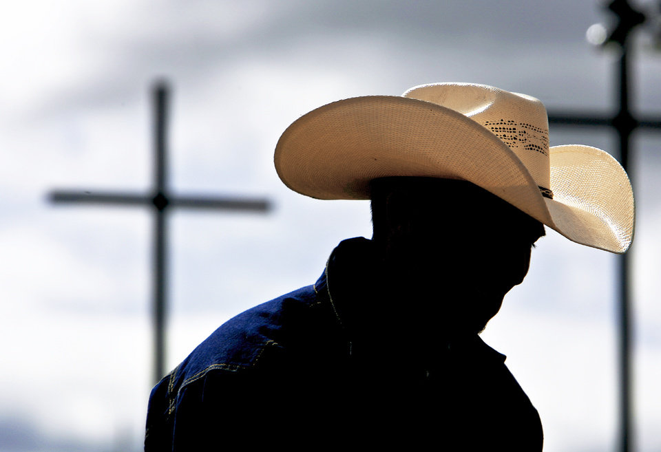 A cowboy sits on the fence rail watching the action during the Youth Rodeo Bible Camp  near Ada.