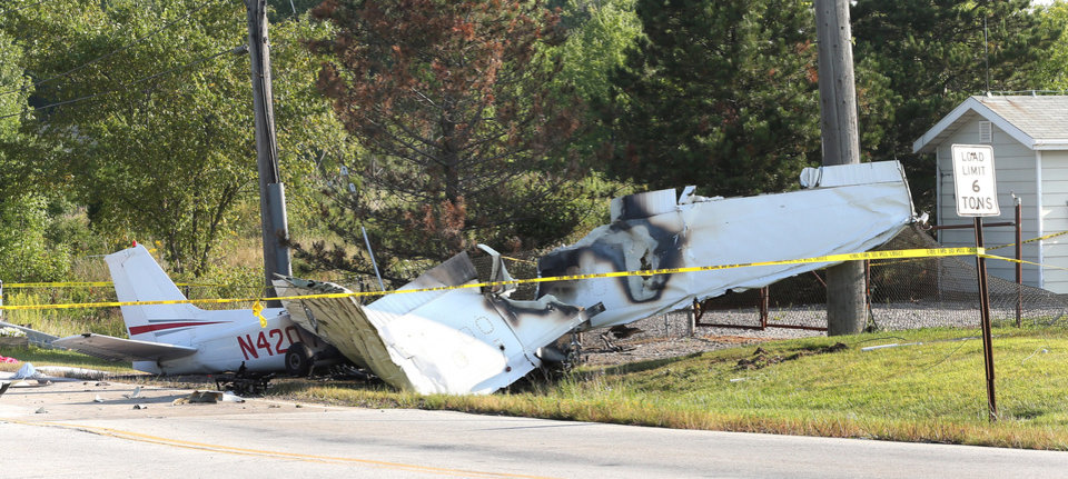 Photo - The wreckage from a plane that crashed rests on the side of a road, Tuesday, Aug. 26, 2014, in Richmond Heights, Ohio. The Cessna 172R crashed and burst into flames just after takeoff Monday night from Cuyahoga County Airport, outside of Cleveland, killing all four people on board, according to the Ohio State Highway Patrol. (AP Photo/The Plain Dealer, Chuck Crow) MANDATORY CREDIT; NO SALES