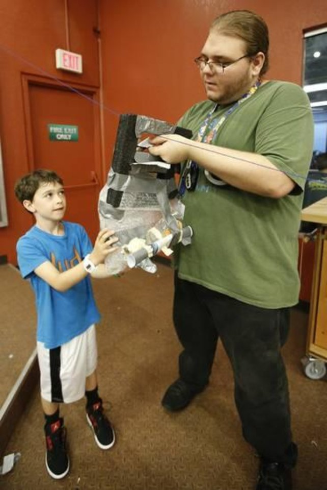 Photo -  Will Blalock,8, prepares to launch his zip line project with the help of Chris Syfrett, floor facilitator in the new Tinkering Garage at Science Museum Oklahoma in Oklahoma City, Thursday July 31 , 2014. Photo By Steve Gooch, The Oklahoman