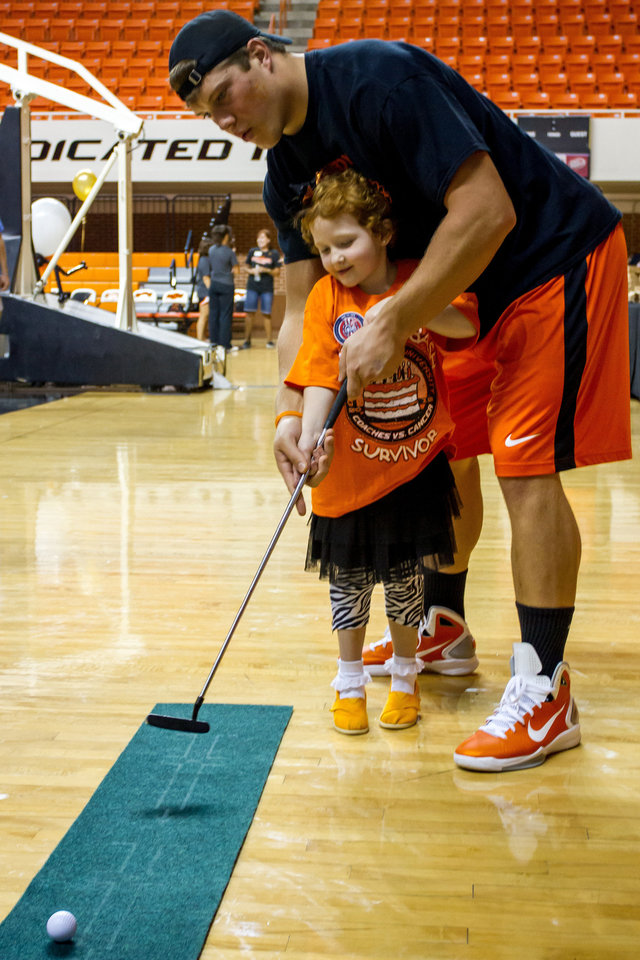 Photo - OSU defensive lineman Cooper Bassett helps Taylor Brandt on the putting green. Oklahoma State University hosted a Coaches vs. Cancer Birthday party in Gallagher-Iba arena in Stillwater on Sept. 16, 2012. PHOTO BY MITCHELL ALCALA, For The Oklahoman  Mitchell Alcala