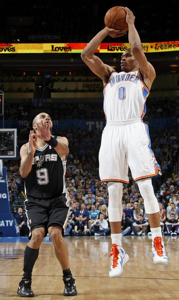 Photo - Oklahoma City's Russell Westbrook (0) takes a shot next to San Antonio's Tony Parker (9) during the NBA basketball game between the Oklahoma City Thunder and the San Antonio Spurs at Chesapeake Energy Arena in Oklahoma City, Friday, March 16, 2012. Photo by Nate Billings, The Oklahoman