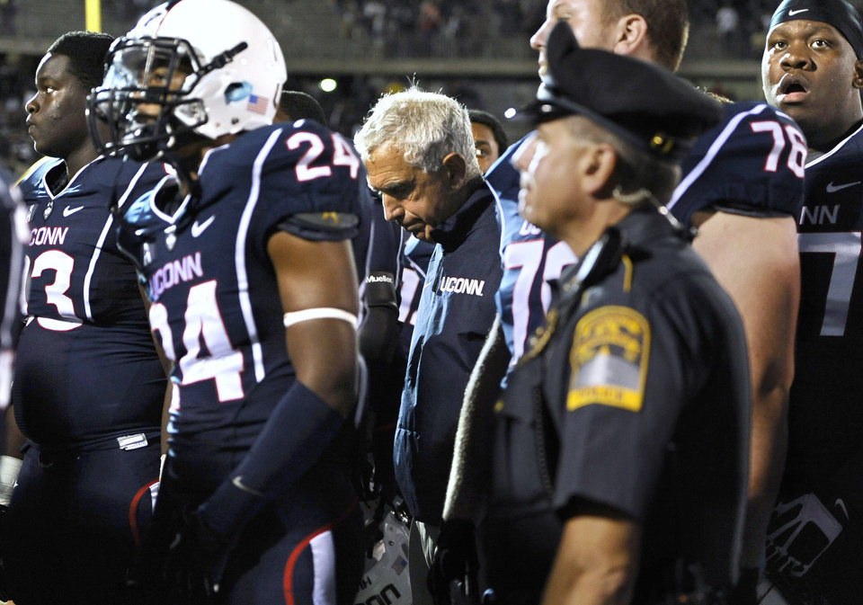 Photo - Connecticut coach Paul Pasqualoni, center, looks down at the end of an NCAA college football game against Michigan at Rentschler Field, Saturday, Sept. 21, 2013 in East Hartford, Conn. Michigan won 24-21. (AP Photo/Jessica Hill)