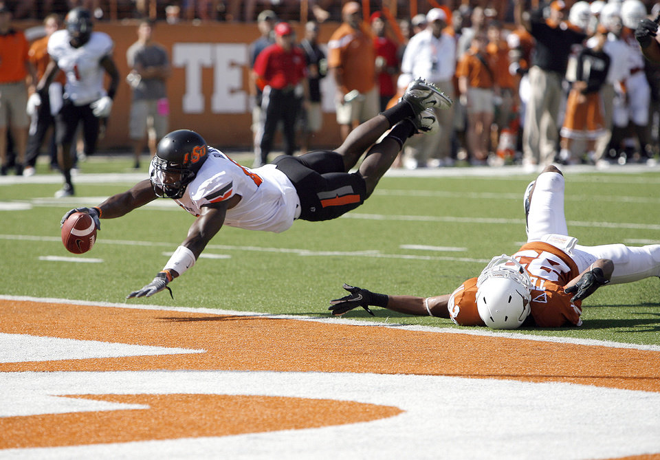 Photo - Oklahoma State's Justin Blackmon (81) dives for a touchdown as Texas' Carrington Byndom (23) defends during first half of a college football game between the Oklahoma State University Cowboys (OSU) and the University of Texas Longhorns (UT) at Darrell K Royal-Texas Memorial Stadium in Austin, Texas, Saturday, Oct. 15, 2011. Photo by Sarah Phipps, The Oklahoman