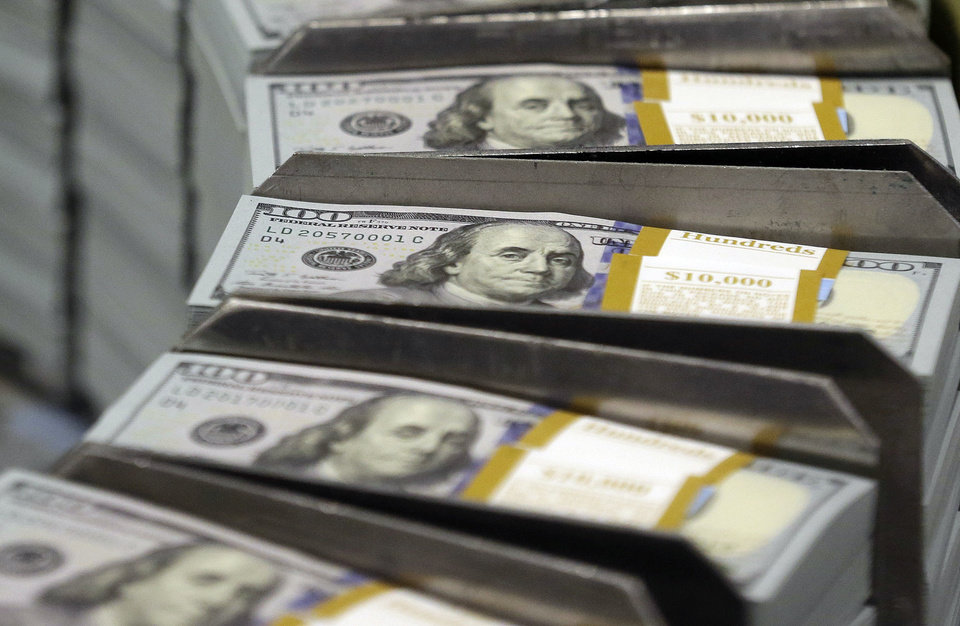 In this Sept. 24, 2013 photo, freshly-cut stacks of $100 bills make their way down the line at the Bureau of Engraving and Printing Western Currency Facility in Fort Worth, Texas. The average 401(k) fee _ a modest-sounding 1 percent _ can wipe $70,000 out of the typical retirement account compared with lower-cost plans that are widely available, according to a new study by a Washington think tank. (AP Photo/LM Otero, File)