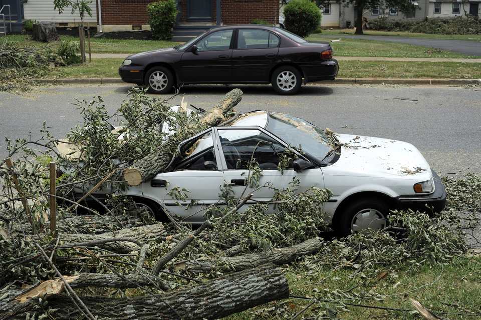 Photo -   A car sits, crushed by a fallen tree, on Carrington Road in Lynchburg, Va., July 1, 2012. Two days after storms tore across the eastern U.S., power outages were forcing people to get creative to stay cool in dangerously hot weather. Temperatures approached 100 degrees in many storm-stricken areas, and utility officials said the power will likely be out for several more days. (AP Photo/The News & Advance, Parker Michels-Boyce)