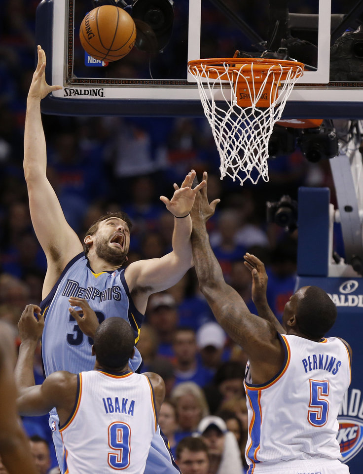 Photo - Memphis' Marc Gasol (33) shoots over Oklahoma City's Serge Ibaka (9) and Kendrick Perkins (5) during Game 7 in the first round of the NBA playoffs between the Oklahoma City Thunder and the Memphis Grizzlies at Chesapeake Energy Arena in Oklahoma City, Saturday, May 3, 2014. Photo by Nate Billings, The Oklahoman