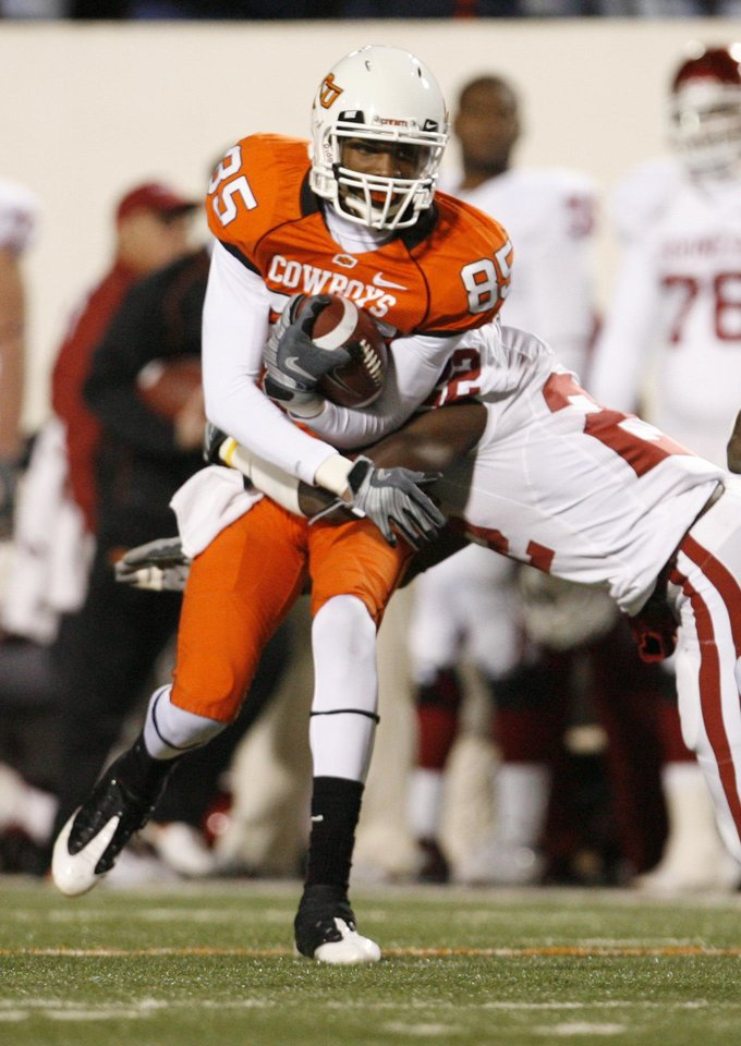 OSU's Damian Davis runs after catch and is hit by Keenan Clayton of OU during the first half of the college football game between the University of Oklahoma Sooners (OU) and Oklahoma State University Cowboys (OSU) at Boone Pickens Stadium on Saturday, Nov. 29, 2008, in Stillwater, Okla. STAFF PHOTO BY NATE BILLINGS