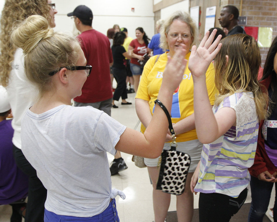 Photo - Briarwood Elementary School fifth graders Emma Ferrell, left, and Bodie Gibson high-five before receiving gifts from Martin Luther King Elementary School in Edison, New Jersey during a get-together at Red Oak Elementary School in Oklahoma City, OK, Saturday, June 15, 2013. Children from the two schools were trading letters before the May 20th tornado destroyed the school. Photo by Paul Hellstern, The Oklahoman
