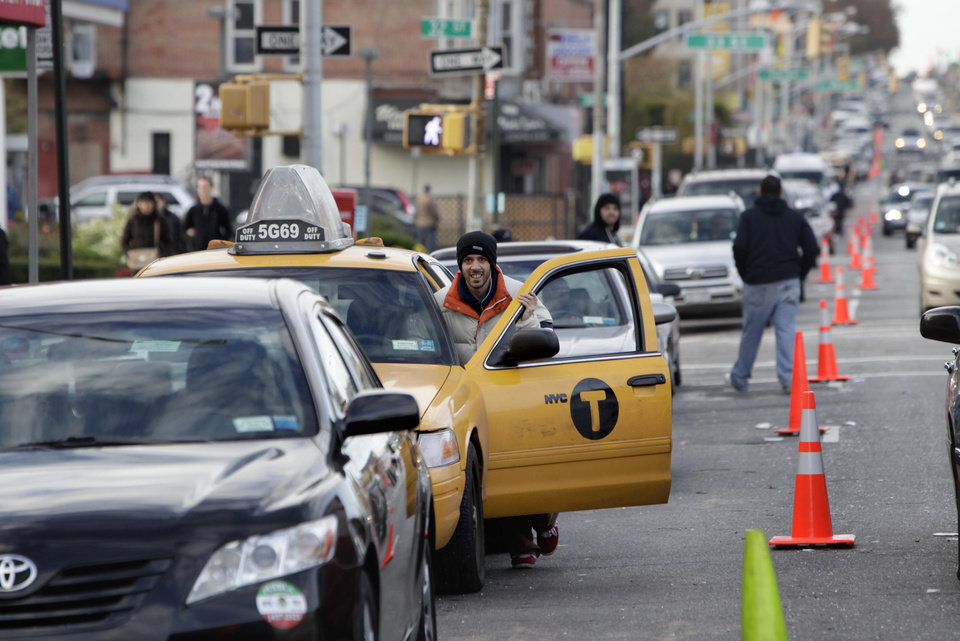 Photo -   A cab driver pushes his taxi cab forward in a line for gasoline in the Brooklyn borough of New York, Friday, Nov. 2, 2012. In parts of New York and New Jersey, drivers face another day of lining up for hours at gas stations struggling to stay supplied. Superstorm Sandy damaged ports that accept fuel tankers and flooded underground equipment that sends fuel through pipelines. Without power, fuel terminals can't pump gasoline onto tanker trucks, and gas stations can't pump fuel into customers' cars. (AP Photo/Seth Wenig)