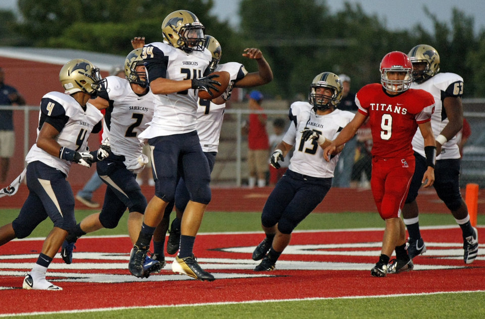 The Southmoore Sabercats celebrate a fumble recovered for a touchdown near Carl Albert's Caleb Toney (9) during a high school football game between Carl Albert and Southmoore in Midwest City, Okla., Friday, Aug. 31, 2012. Photo by Nate Billings, The Oklahoman