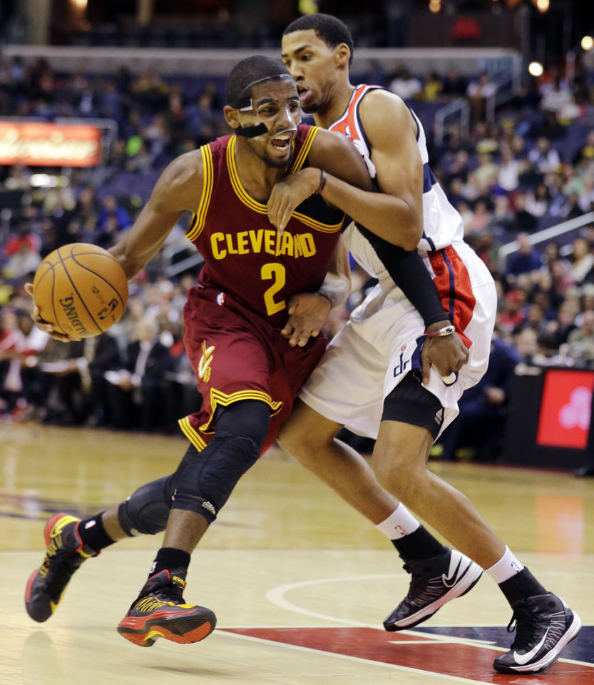 Photo - Cleveland Cavaliers guard Kyrie Irving (2) drives against Washington Wizards guard Garrett Temple in the first half of an NBA basketball game, Wednesday, Dec. 26, 2012, in Washington. (AP Photo/Alex Brandon)