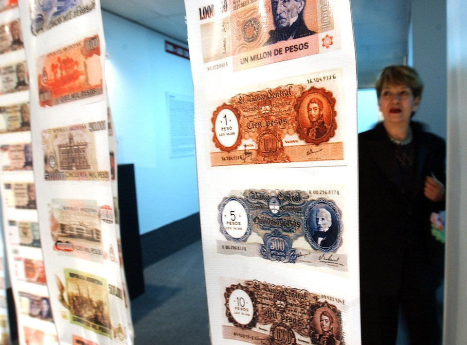 Photo - FILE - In this April, 28, 2005, file photo, a woman looks at old currency during the opening of the Foreign Debt Museum in Buenos Aires, Argentina.  The museum, which is the world's first dedicated to a country's debt, opened nearly four years after Argentina staged the largest debt default in modern history. Argentine President Cristina Fernandez said Monday June 16, 2014 that Argentina can't comply with U.S. court orders to pay $1.5 billion to winners of a decade-long legal battle over defaulted debt, the position her country was left in Monday when the U.S. Supreme Court refused to hear her government's final appeal. (AP Photo/Natacha Pisarenko,File)